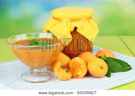 Apricot jam in glass jar and fresh apricots, on wooden table, on bright background
