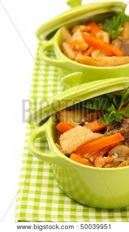 Homemade beef stir fry with vegetables in color pans, isolated on white