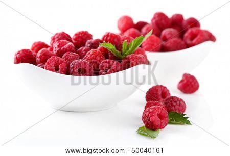 Ripe sweet raspberries in bowls, isolated on white