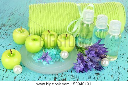 Hand made soap and aroma candles on green wooden background