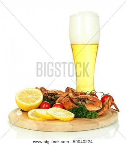 Boiled crabs with lemon slices and tomatoes, on wooden board, isolated on white