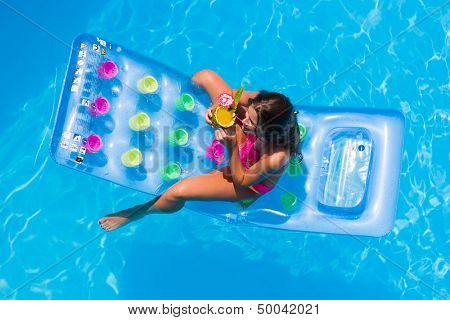 Top view of a  girl with cocktail on a lilo in the swimming pool