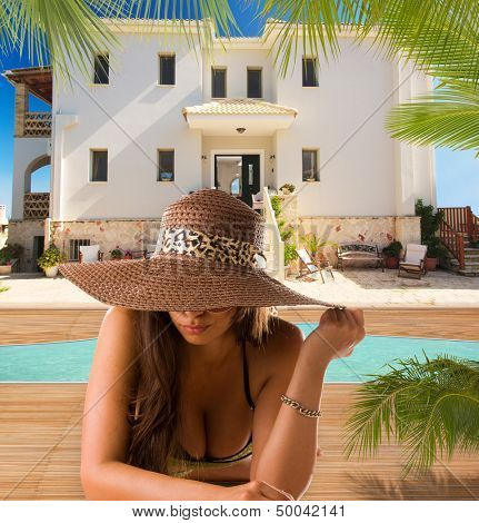 Woman by the swimming pool at luxury tropical resort