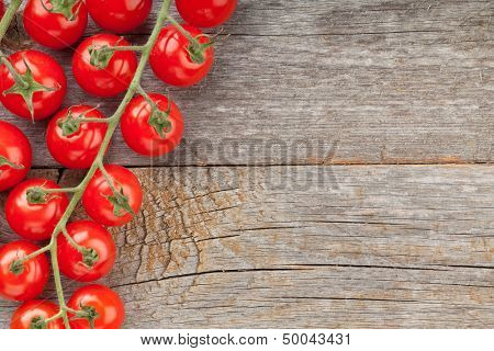 Wood table with cherry tomatoes and copyspace