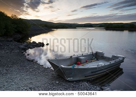 Beautiful Moody Sunrise Over Calm Lake With Boat On Shore