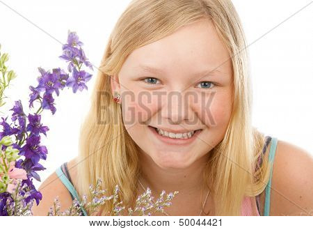 Portrait of a beautiful blond, blue-eyed teenage girl with flowers, on a white background.
