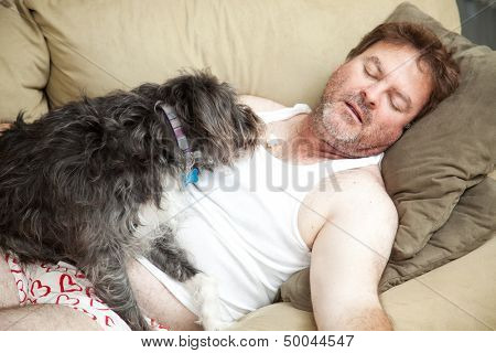 Unemployed man passed out on the couch in his underwear.  His dog is eating popcorn from his chest.