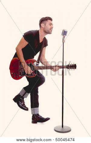 rock star singing with guitara and micorphone