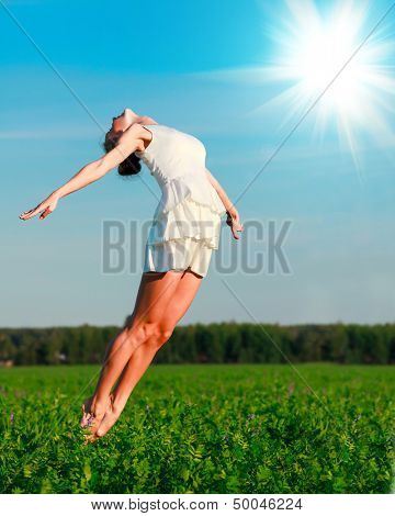 Woman jumps in a green field