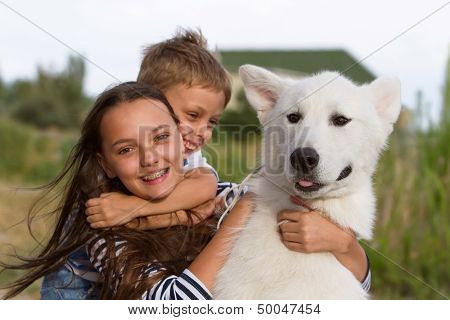 Happy kids playing with their snow white malamute dog