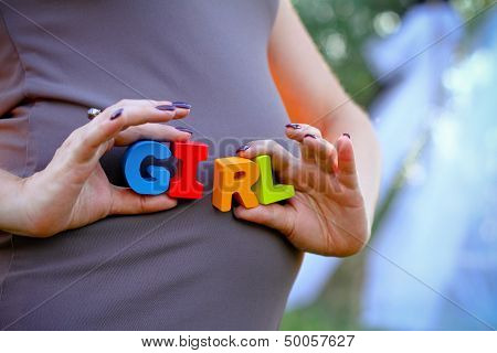 Pregnant Woman Holding The Word Girl