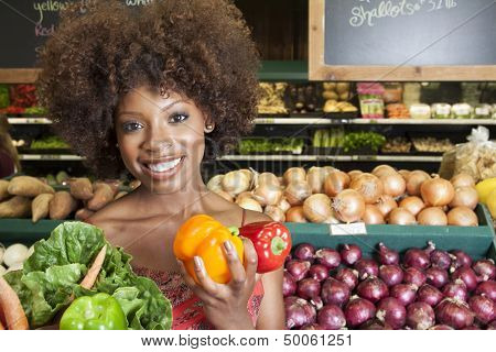 African American woman holding bell peppers and vegetables at supermarket
