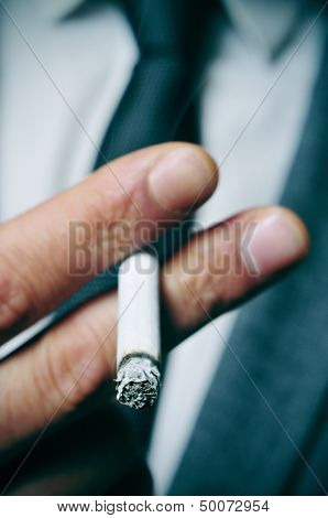 a man wearing a suit smoking a cigarette