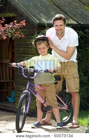 Father Putting Saftey Helmet On Son Before Bike Ride