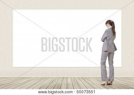 Asian elegant business woman standing and looking at blank white banner, board, placard or poster. Copy-space for advertise.
