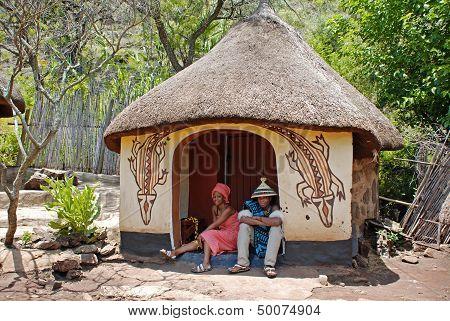 Sotho Couple Wearing Tribal Handmade Dress Sitting Near Traditional Native House.