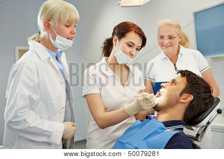 Dental assistant taking approbation test with two dentists