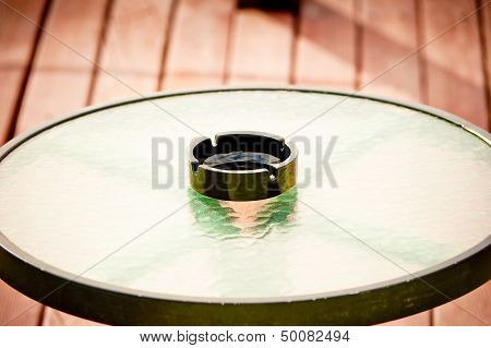 black empty ashtray stands in the middle of a round glass table