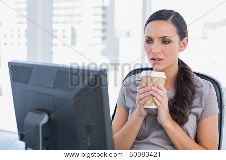 Unsmiling attractive businesswoman in her office holding coffee