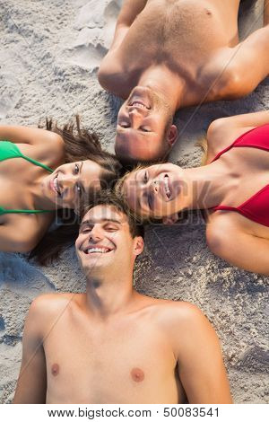 Overhead of smiling friends lying together in a circle on the beach