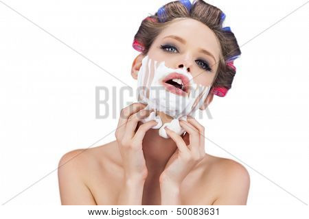 Sensual young model with shaving foam looking at camera on white background