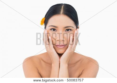 Sensual model with orange flower in hair touching her face on white background