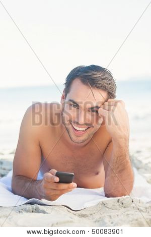 Smiling handsome man relaxing on the beach holding his cellphone
