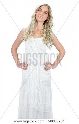 Cheerful gorgeous model in white dress posing on white background