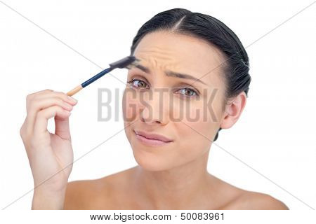 Uneasy young model using eyebrow brush on white background