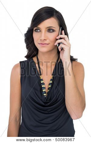 Elegant brown haired model with black classy clothes posing holding smartphone on white background