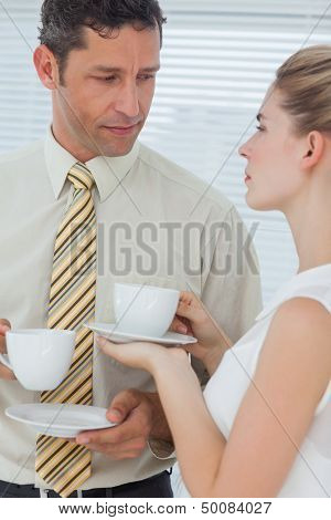 Stylish colleagues having coffee together in break room