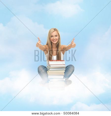 education concept - smiling student with stack of books sitting on the cloud