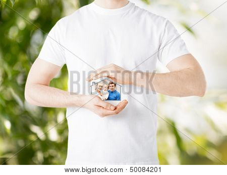 home, real estate, family and technology concept - man and sign of family with child and dream house