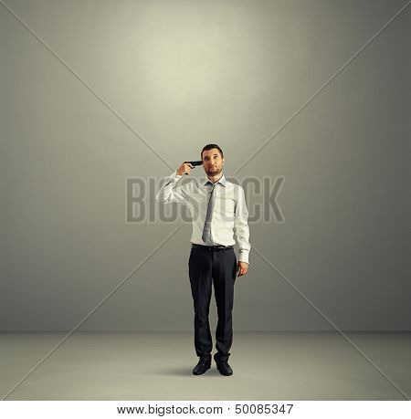full length shot of quiet businessman with gun in dark room
