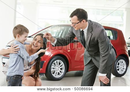 At automobile sales centre. Car salesperson selling new automobile to young family with child boy