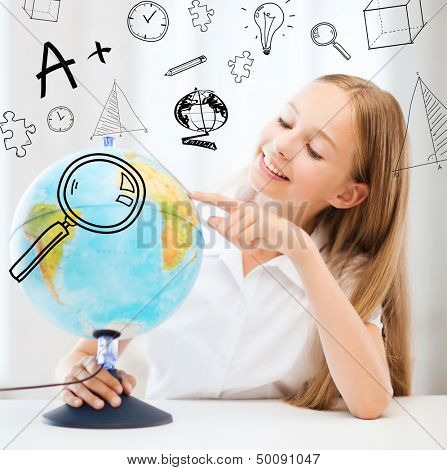 education and school concept - little student girl with globe at school