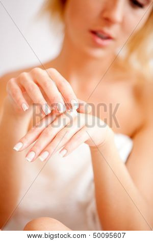 Young woman applies cream on hands over white, focus on hands