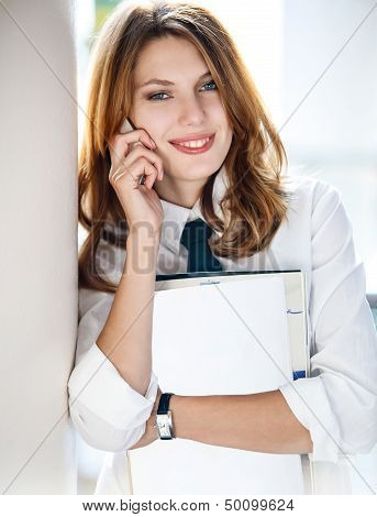 Beautiful young business woman holding folder in her hand and talking on the phone