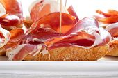 closeup of a plate with some typical spanish pinchos de jamon, serrano ham served on bread poster