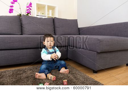 Asian baby boy playing toy block at home