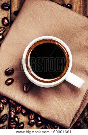 Cup Of Coffee With Coffee Beans On  Brown Napkin On Wooden Background. White Cup Of Espresso, Top Vi