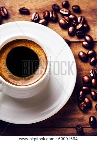 Coffee Cup With White Saucer And Roasted Coffee Beans  On Wooden  Brown Background, View From Above.