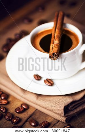 Coffee Cup And Coffee Beans With Cinnamon Sticks On Wooden  Brown Background, Close Up. Coffee  On A