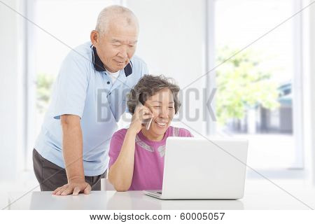 Senior Couple Using A Laptop And A Phone  At Home