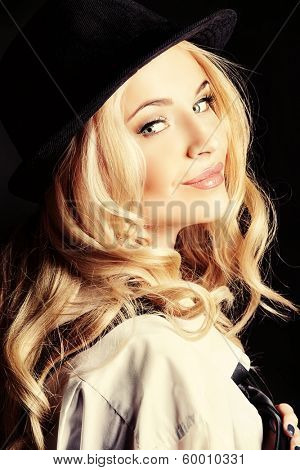 Elegant blonde woman wearing white shirt and black hat and tie. Over dark background.