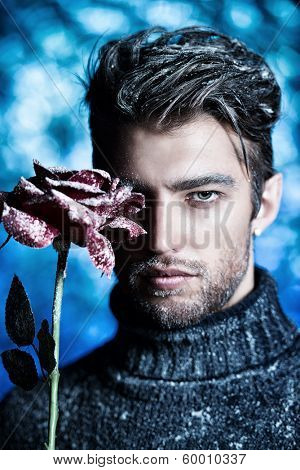Portrait of a handsome man dressed in winter clothes, holding a rose, covered with snow.