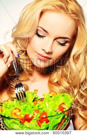 Portrait of a beautiful young woman eating vegetable salad. Healthy life. Diet.