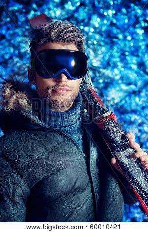Portrait of a handsome man dressed in winter clothes, holding skiing, covered with frost.