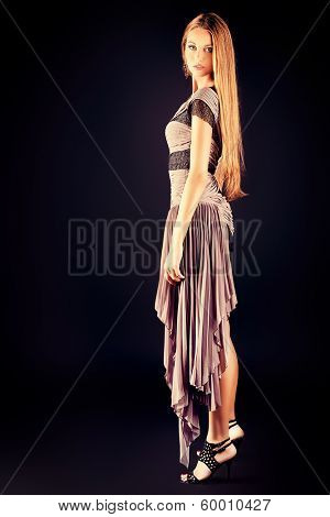 Full length portrait of a fashionable model in an evening dress.