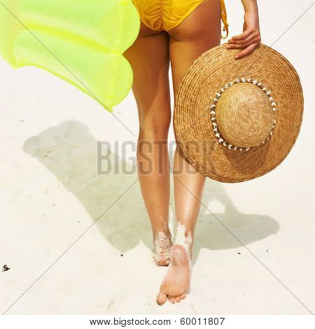 Woman with yellow inflatable raft walking at the beach